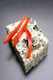 Blue cheese and red pepper. Details of a block of blue cheese and slices of red pepper.  Narrow depth of field Royalty Free Stock Image