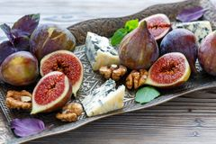 Blue cheese and ripe figs on a bronze tray. Stock Image