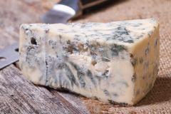 Blue cheese on sackcloth close up on an old wooden table Stock Photos