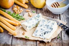 Blue cheese slices with breadsticks, nuts and honey Stock Images