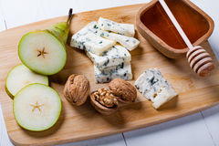 Blue cheese with slices of pear, nuts and honey. Stock Photo