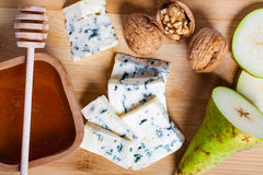 Blue cheese with slices of pear, nuts and honey. Royalty Free Stock Photography