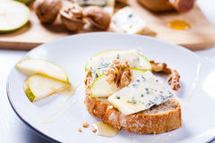 Blue cheese with slices of pear, nuts and honey. Royalty Free Stock Images