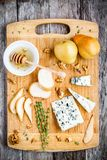 Blue cheese with slices of pear, nuts and honey top view Royalty Free Stock Photography