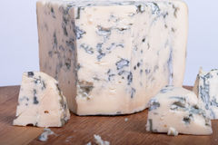 Blue cheese with slices on wooden board. Shallow depth of field Stock Photo