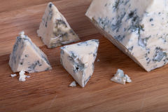 Blue cheese with slices on wooden board. Shallow depth of field Royalty Free Stock Photo