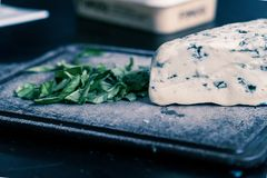 Blue cheese with spinach on cutting board Royalty Free Stock Images