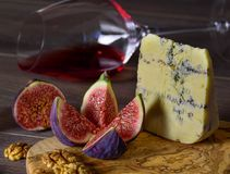 Blue cheese and sweet fruit figs, walnut and wineglass with red stock images