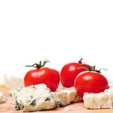 Blue Cheese and Tomatoes Closeup. Danish blue cheese closeup with tomatoes on white background Royalty Free Stock Photos