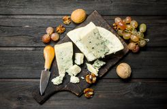 Blue cheese with walnuts and grapes. On a wooden background royalty free stock images