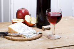 Blue cheese and wine. Fresh blue cheese with a glass of red wine and an apple on wooden table royalty free stock photography