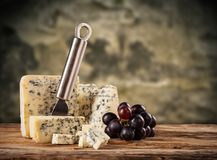 Blue cheese on wood. Still life of blue cheese served on wood in cellar royalty free stock image