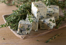 Blue cheese on a wooden table . Blue cheese and branches of thyme on a wooden table royalty free stock photo