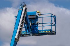 Blue cherry picker machine against blue sky background. Rear view of a blue cherry picker machine against blue sky background royalty free stock photos