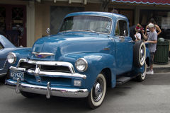 Blue Chevy pickup truck near the cafe. Front view. Saratoga, California, United States - July 19, 2015: A man helping a girl to leave the vintage Chevy pickup stock photography