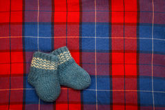 Blue children`s knitted wool socks for a newborn on tartan. chec. Kered background with socks. the concept of children`s clothing Royalty Free Stock Photos