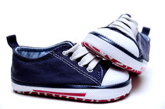 Blue childrens sneakers. A pair of blue childrens sneakers with white laces and red trim Stock Images