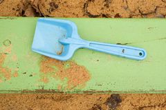 Blue children shovel toy on white sand, plastic play for game. Mound of sand in kindergarden. Stock Photography