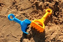 Blue childrens spatula and yellow rake, stuck in sand Stock Image