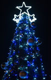 Blue Christmas. An outdoor shot of a large blue lit christmas tree at night on a black background Stock Image