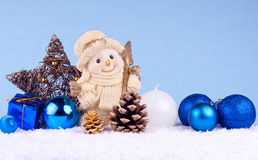 Blue christmas background. Snowman with xmas balls, candle, oak ball and star on blue background stock photography