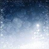 Blue christmas background. Blue  christmas background of christmas tree, smow and snowflakes border Royalty Free Stock Images