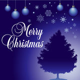 Blue Christmas background. A blue Christmas background with snowflakes and ornaments, a silhouetted Christmas tree and the words Merry Christmas in white Stock Photo