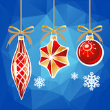 Blue christmas background. Three Christmas toys on a blue polygonal background Royalty Free Stock Photos