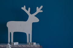 Blue Christmas background with white wooden deer Stock Photos