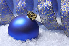 Blue christmas ball. With a curly golden blue ribbon in snow Royalty Free Stock Photography