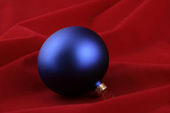 Blue christmas ball. On the red background Royalty Free Stock Photo