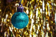 Blue Christmas ball on a background of a yellow garland. Celebration royalty free stock image