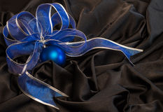 Blue Christmas ball with a blue ribbon on  black satin fabric wi Royalty Free Stock Photo