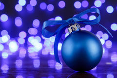 Blue christmas ball and blured purple lights at the background Stock Photography