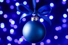 Blue christmas ball and blured purple lights at the background Royalty Free Stock Images