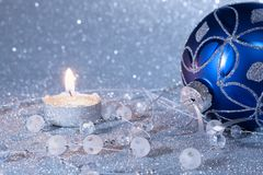 Blue Christmas ball and candle on a silver background. New Year`s composition. stock images