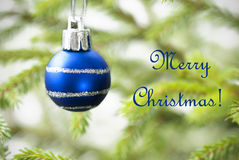 Blue Christmas Ball on Christmas Tree with Text Merry Christmas Royalty Free Stock Image