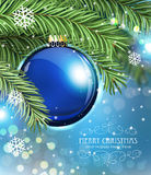 Blue Christmas ball. And fir tree branches on a sparkling  holiday background. Festive Christmas background Stock Photography
