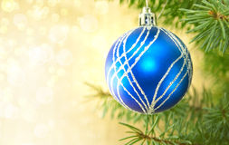 Blue Christmas ball and green tree on shiny background with copy. Space for text. Christmas background or greeting card. Selective focus Stock Image