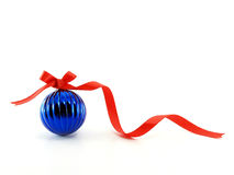 close up blue glossy christmas ball with red ribbon bow isolated on white background Royalty Free Stock Photos