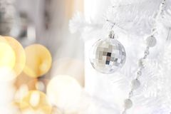 Shiny silver Christmas ball on a christmas tree on silver background with bokeh effect for New Year`s greetings. Blue Christmas ball on a silver background with royalty free stock photos