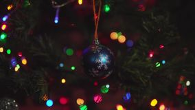 Blue Christmas ball with silver snowflakes rotate on branch artificial pine. stock video