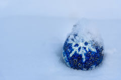 Blue Christmas Ball on snow. Blue Christmas Ball with snowflake on white snow in winter Stock Image