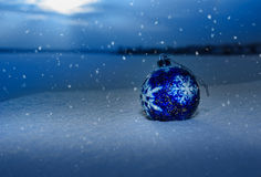 Blue Christmas Ball on snow. Blue Christmas Ball with snowflake on white snow in winter Royalty Free Stock Image
