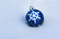 Blue Christmas Ball on snow. Blue Christmas Ball with snowflake on white snow in winter Royalty Free Stock Images