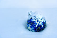 Blue Christmas Ball on snow. Blue Christmas Ball with snowflake on white snow in winter Royalty Free Stock Photo