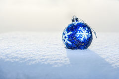 Blue Christmas Ball on snow. Blue Christmas Ball with snowflake on white snow in winter Stock Images