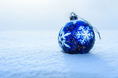 Blue Christmas Ball on snow. Blue Christmas Ball with snowflake on white snow in winter Stock Photography
