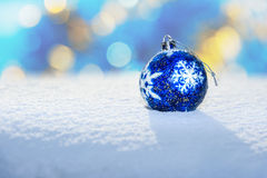 Blue Christmas Ball on snow. Blue Christmas Ball with snowflake on white snow in winter. Christmas background Royalty Free Stock Image