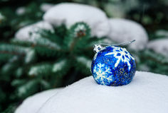 Blue Christmas Ball on snow. Blue Christmas Ball on white snow in winter . Green christmas tree background Stock Photography